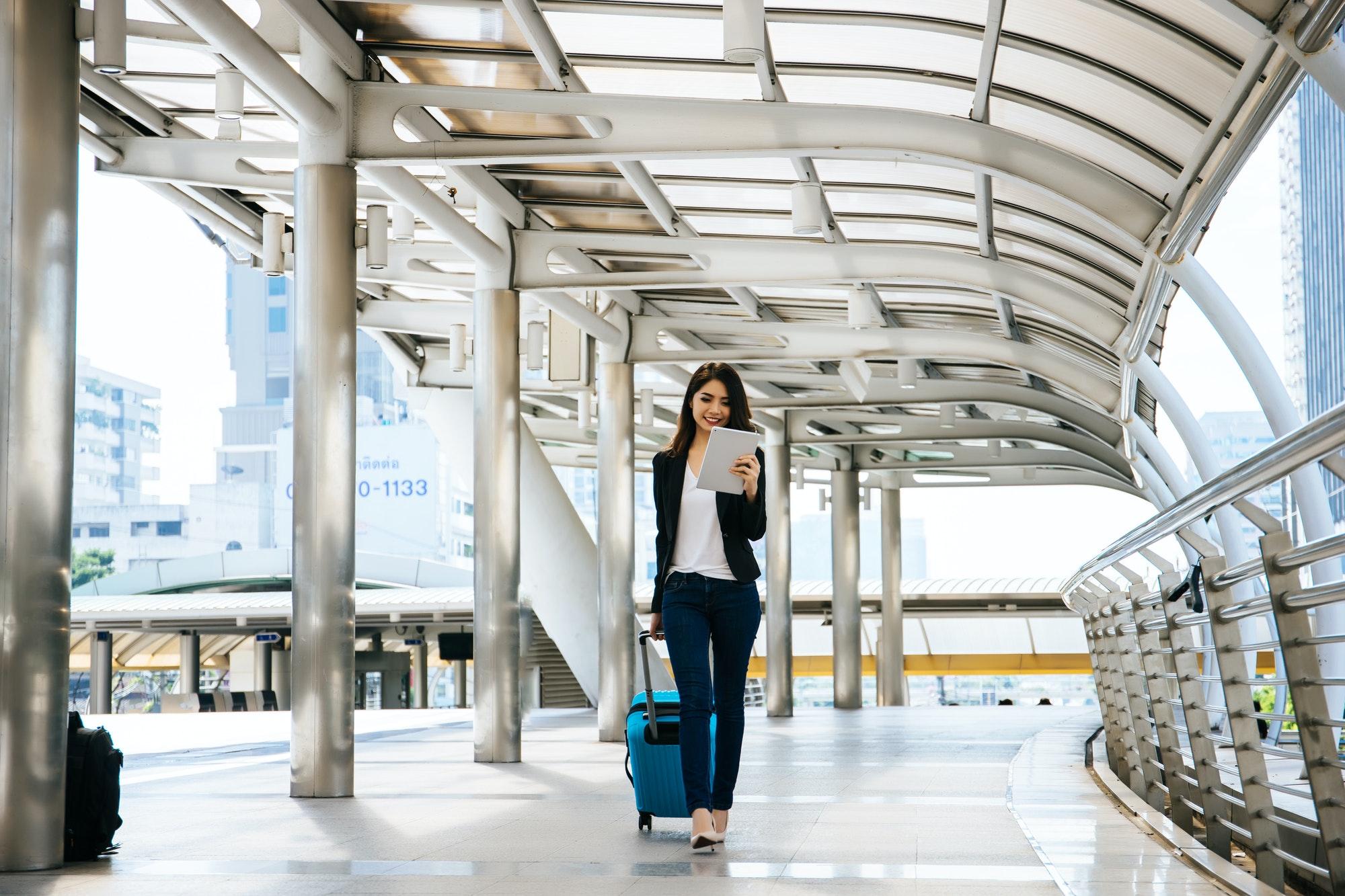 businesswoman walking outside public transportation station businesswoman traveler with suitcase