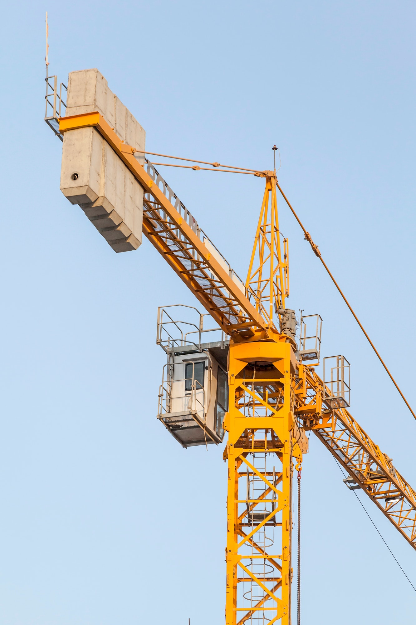 yellow construction crane against the blue sky infrastructure